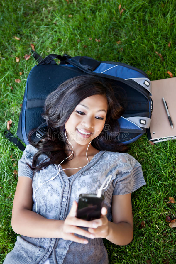 Studente di college asiatico che ascolta la musica fotografia stock