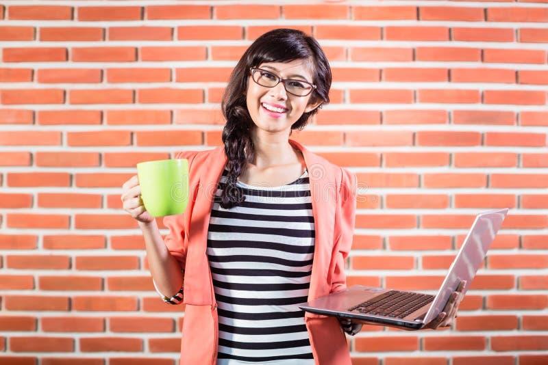 Studente di college asiatico con il computer portatile ed il caffè immagini stock libere da diritti