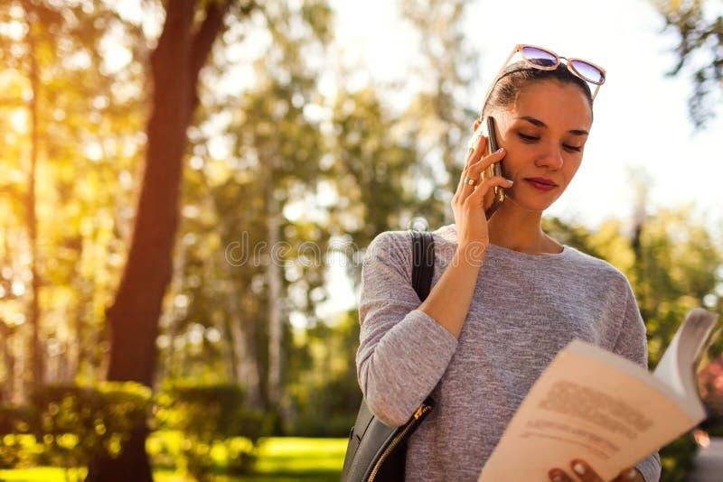 Studente di college che parla sul telefono cellulare in parco Giovane donna che controlla informazioni in libro immagini stock