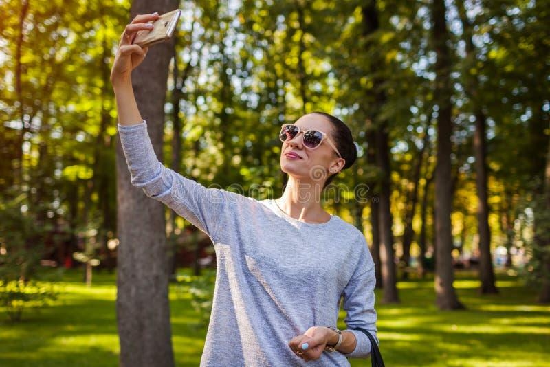 Studente di college che prende selfie sul telefono cellulare in parco Occhiali da sole da portare della giovane donna fotografia stock