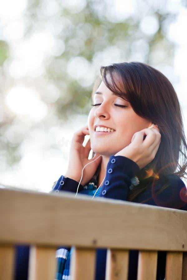 Studente di college della corsa Mixed che ascolta la musica immagini stock libere da diritti