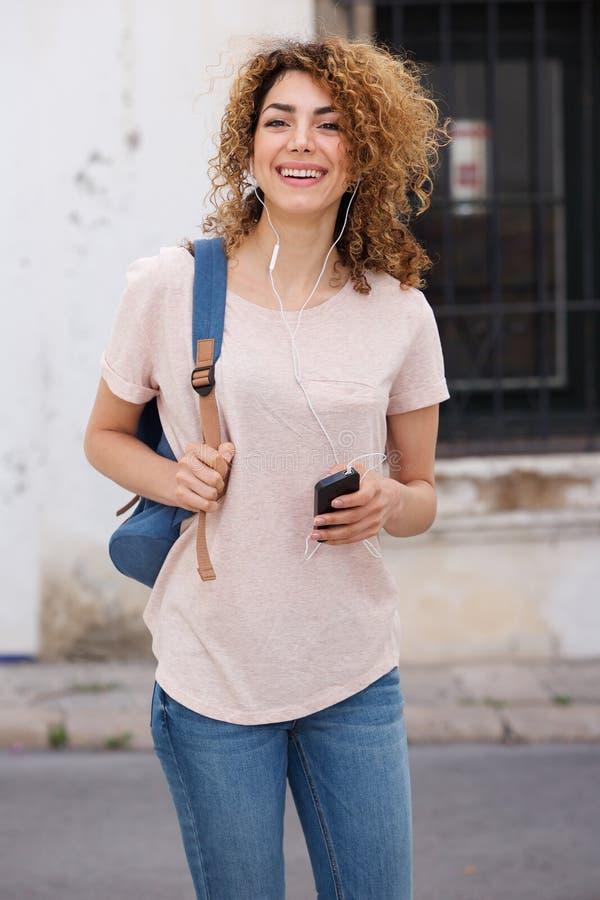 Studente di college femminile che cammina fuori con il telefono cellulare e le cuffie fotografia stock