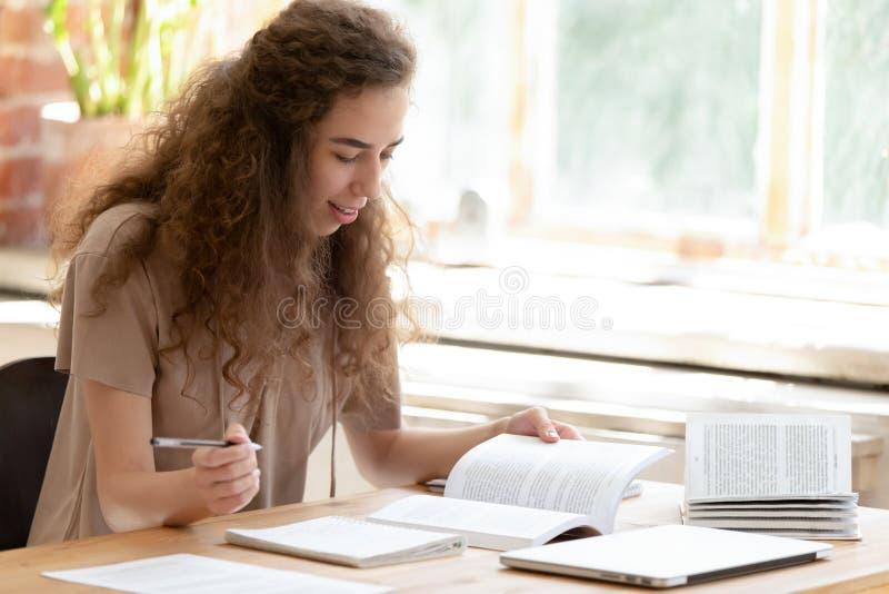 Studente di college teenager della ragazza che studia i manuali della lettura che imparano facendo le note fotografia stock libera da diritti