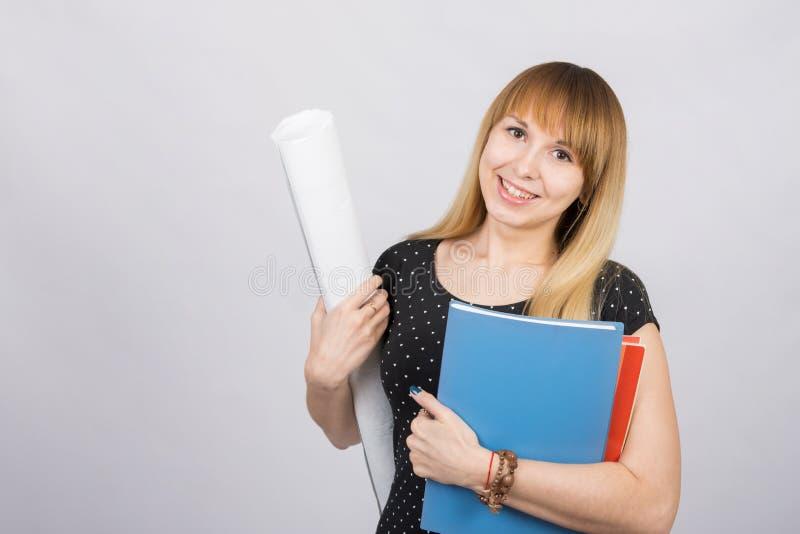 Studente die en blauwdrukken en een omslag met documenten glimlachen houden stock foto