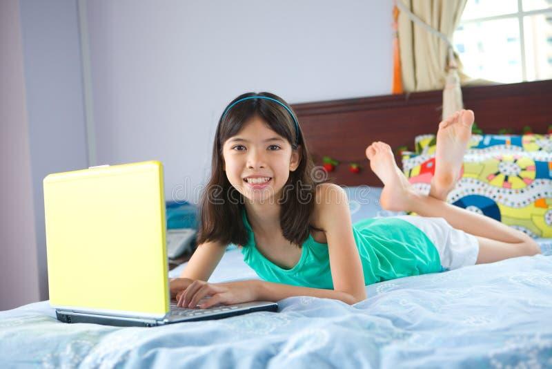 Studente die laptop in slaapkamer met behulp van royalty-vrije stock foto