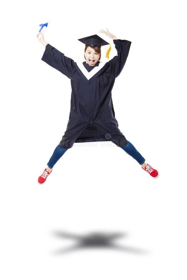 Studente felice in abito laureato che salta contro il bianco indietro fotografia stock libera da diritti