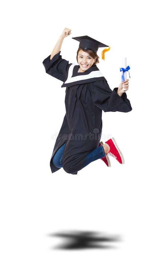 Studente felice in abito laureato che salta contro il bianco indietro immagini stock
