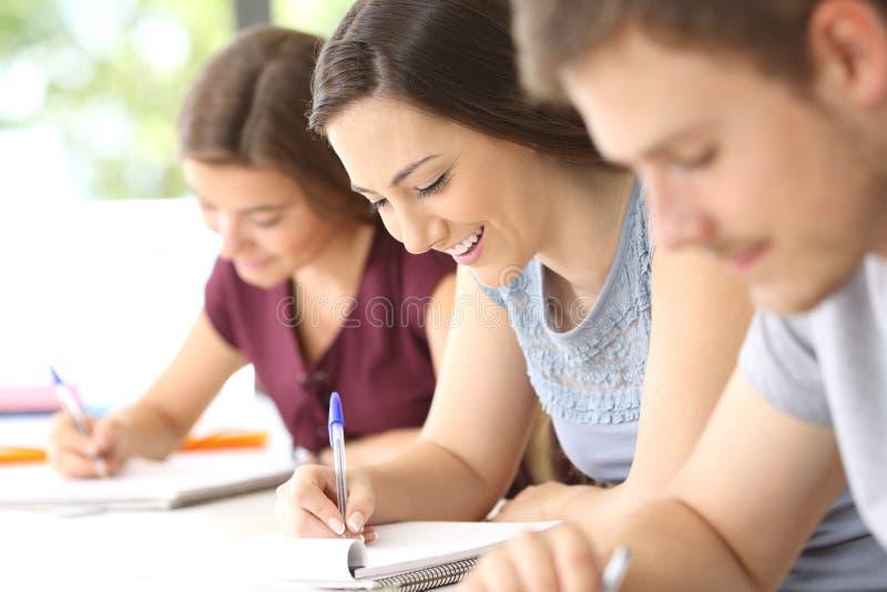 Studente felice che prende le note in aula fotografie stock