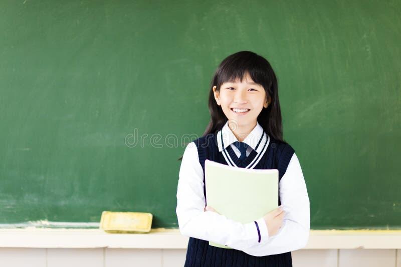 Studente felice con il libro in aula fotografia stock