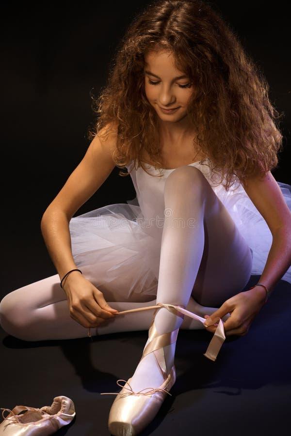 Studente grazioso di balletto che lega pizzo sulla scarpa immagini stock