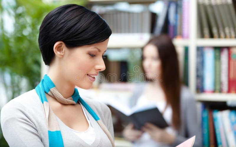 Studente grazioso di signora alla biblioteca contro gli scaffali per libri immagini stock