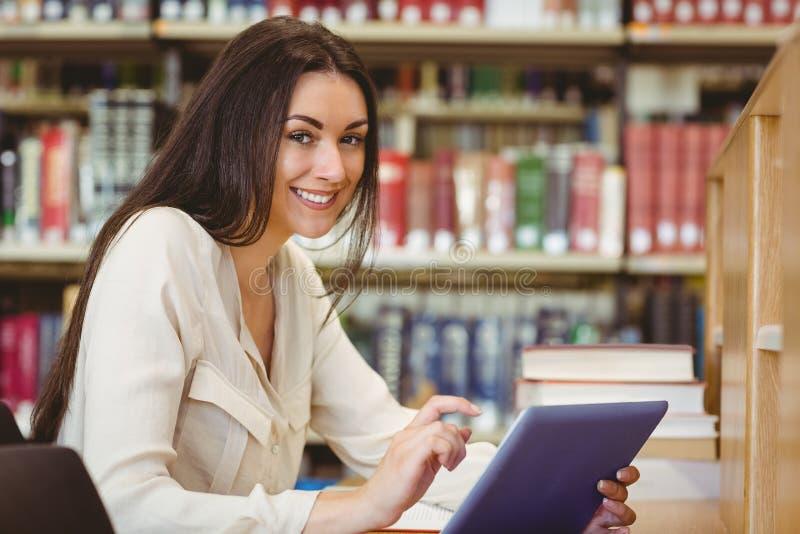 Studente grazioso sorridente che per mezzo del computer della compressa fotografie stock libere da diritti