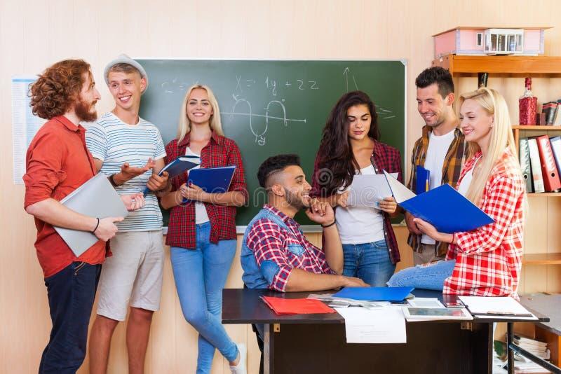 Studente High School Group che discute l'aula dell'università, comunicazione casuale dei giovani fotografie stock libere da diritti