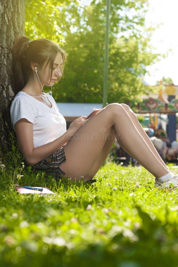 Studente incantante Girl Sitting su erba verde immagini stock libere da diritti
