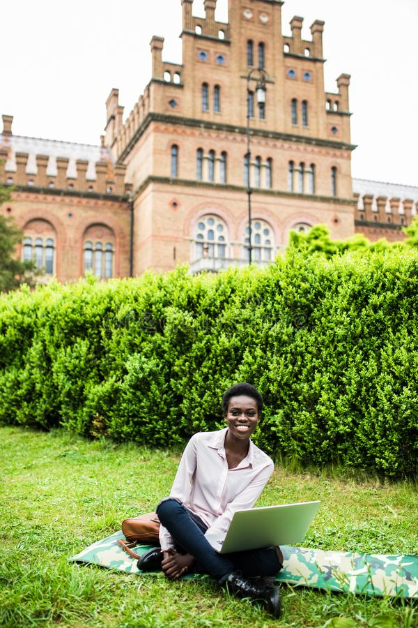 Studente internazionale afroamericano felice che scrive sul computer portatile che prepara per l'esame all'aperto nella città uni immagine stock libera da diritti