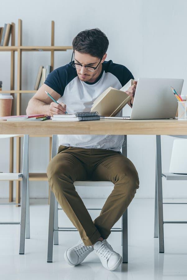 studente maschio bello in vetri che studia con il libro immagini stock