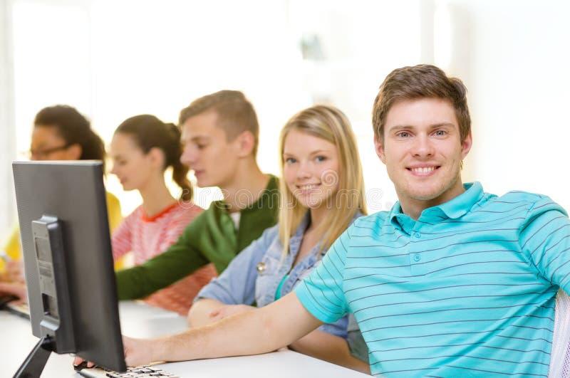 Studente maschio con i compagni di classe nella classe del computer immagini stock