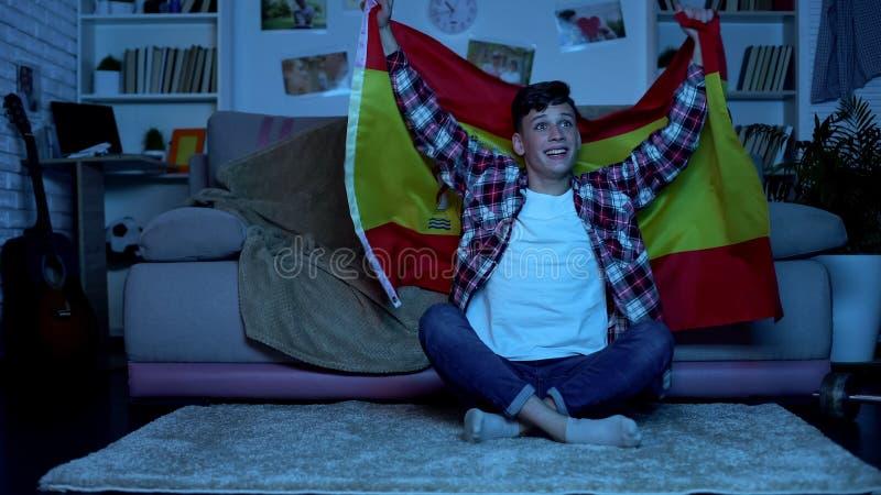 Studente maschio con la bandiera spagnola che incoraggia e che sostiene squadra di calcio nazionale fotografia stock