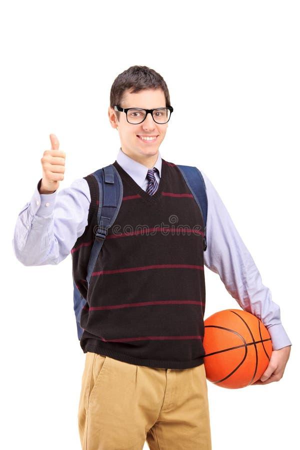 Studente maschio con la borsa di scuola che tiene una pallacanestro e che dà Thu immagini stock