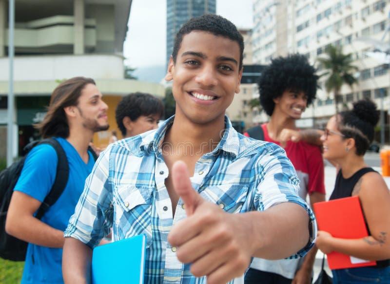 Studente maschio dei pantaloni a vita bassa che mostra pollice con il gruppo di multi yo etnico fotografia stock