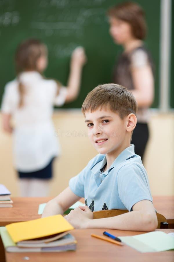 Studente maschio della scuola primaria in aula con il compagno di classe e l'insegnante immagine stock libera da diritti