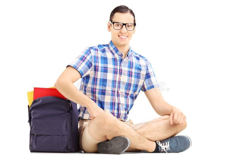 Studente maschio sorridente che si siede su un pavimento con la borsa ed i libri immagine stock