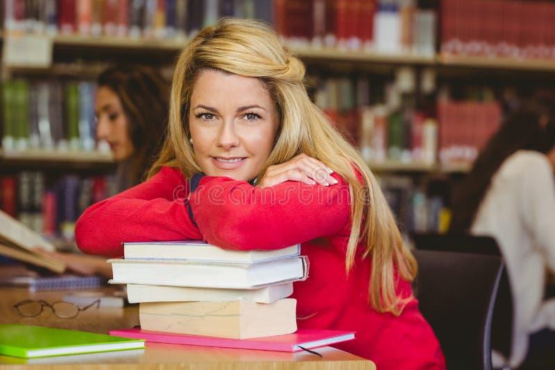 Studente maturo sorridente che si appoggia una pila di libri fotografie stock libere da diritti