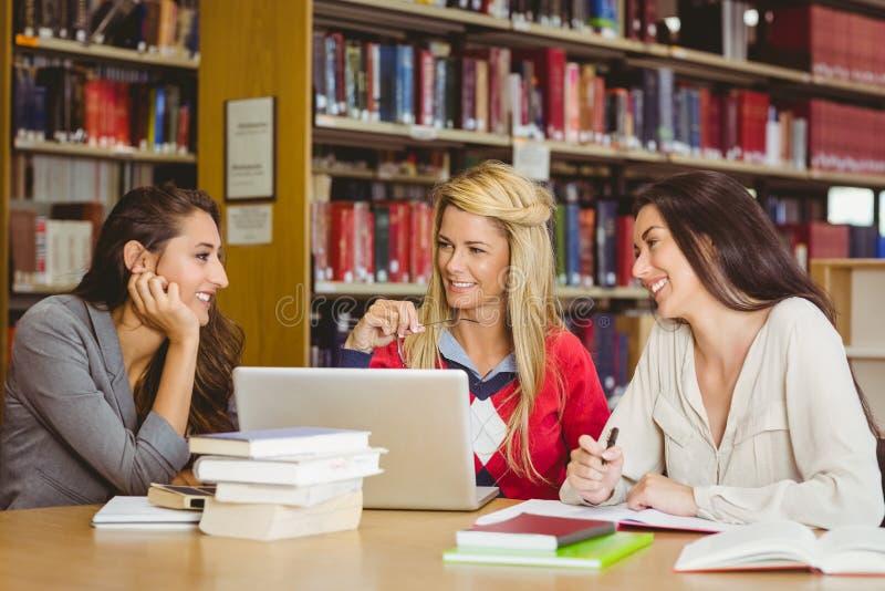 Studente maturo sorridente con i compagni di classe che per mezzo del computer portatile immagini stock