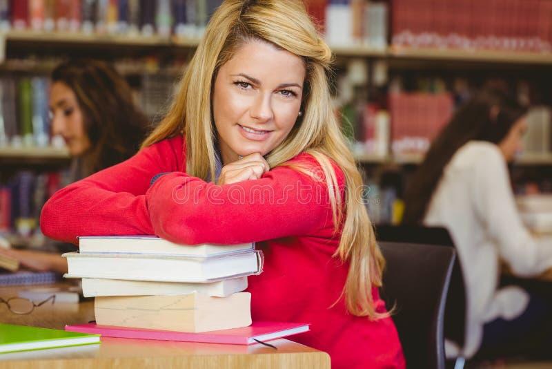 Studente maturo sorridente con la pila di libri fotografia stock libera da diritti