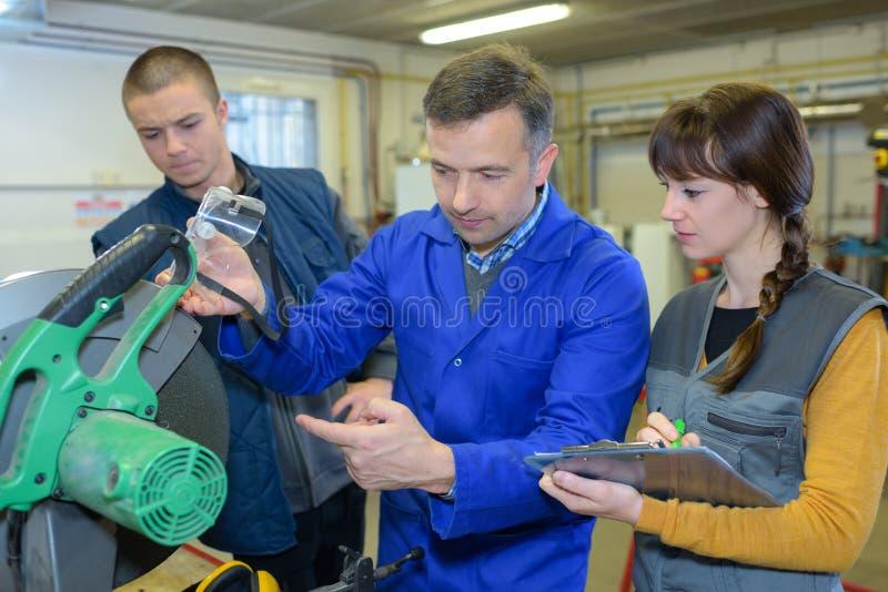 Studente nella classe delle industrie siderurgiche facendo uso della sega circolare immagini stock libere da diritti