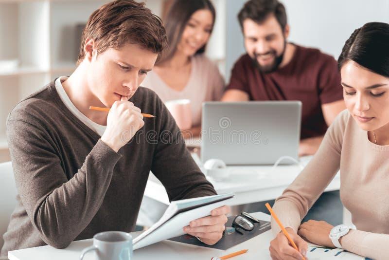 Studente premuroso piacevole che esamina le sue note immagine stock