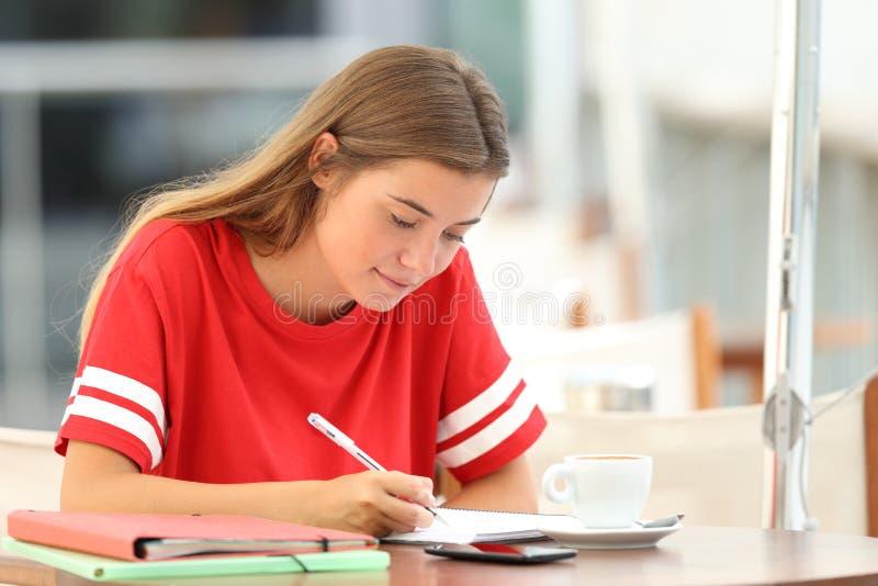 Studente serio che studia prendendo le note in una barra fotografia stock libera da diritti