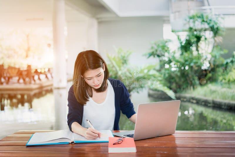Studente Serious Writing della ragazza con le cartelle libro e computer portatile della scuola fotografia stock libera da diritti