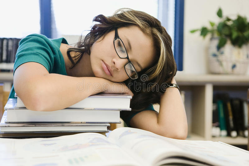 Studente Sleeping della High School su una pila di libri fotografia stock
