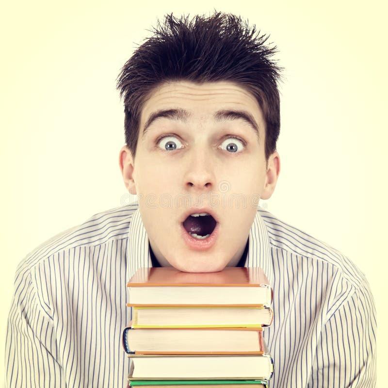 Studente sorpreso con i libri fotografie stock