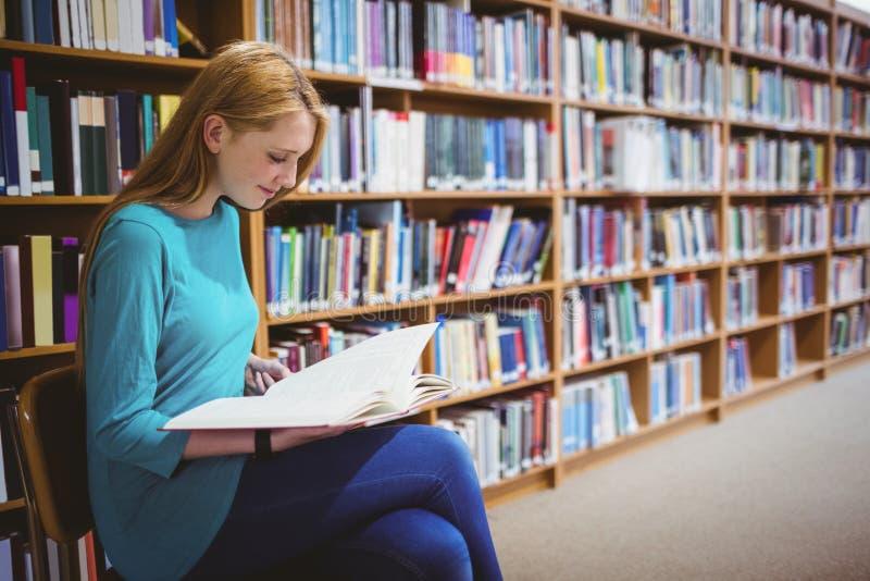 Studente sorridente che si siede sul libro di lettura della sedia in biblioteca fotografie stock