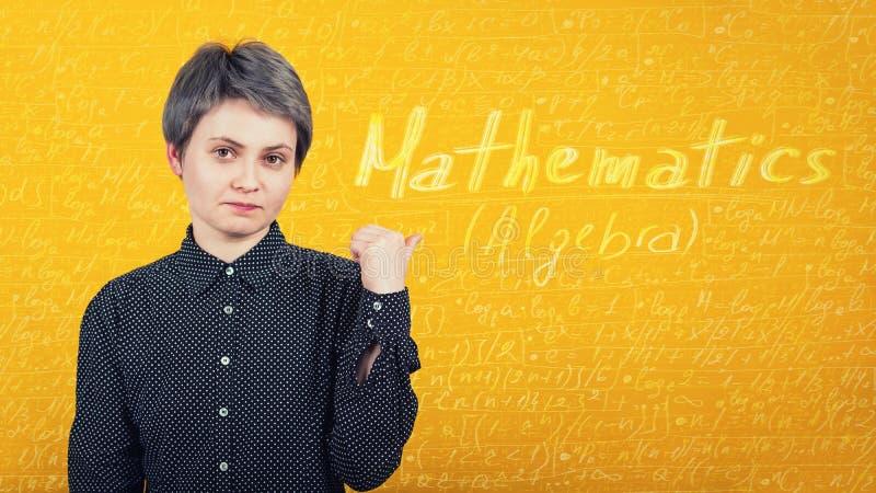 Studente stanco di apprendimento, indicando dito una parete gialla con le formule e le equazioni scritte di matematica Concetto d fotografia stock