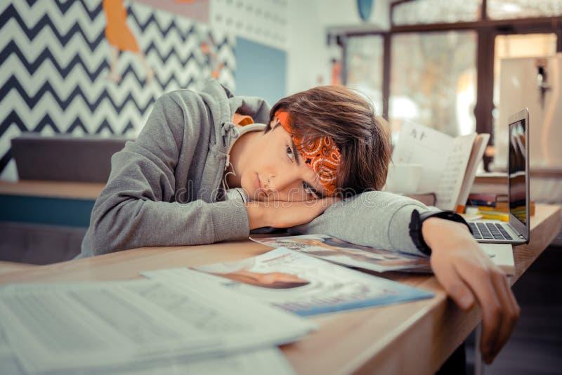 Studente stanco stesso che mette sullo scrittorio fotografia stock