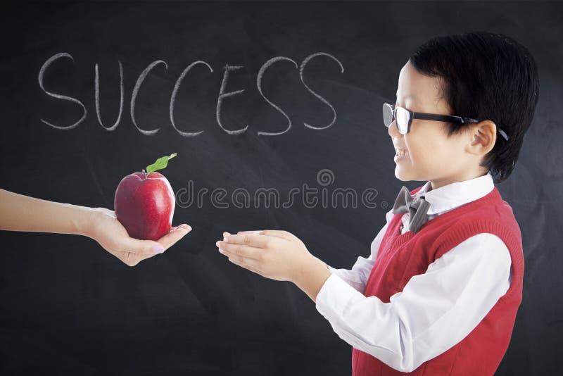 Studente sveglio che ottiene la frutta della mela fotografie stock libere da diritti