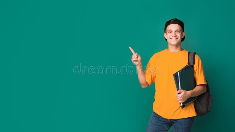 Studente teenager con i libri che indica sullo spazio della copia immagini stock