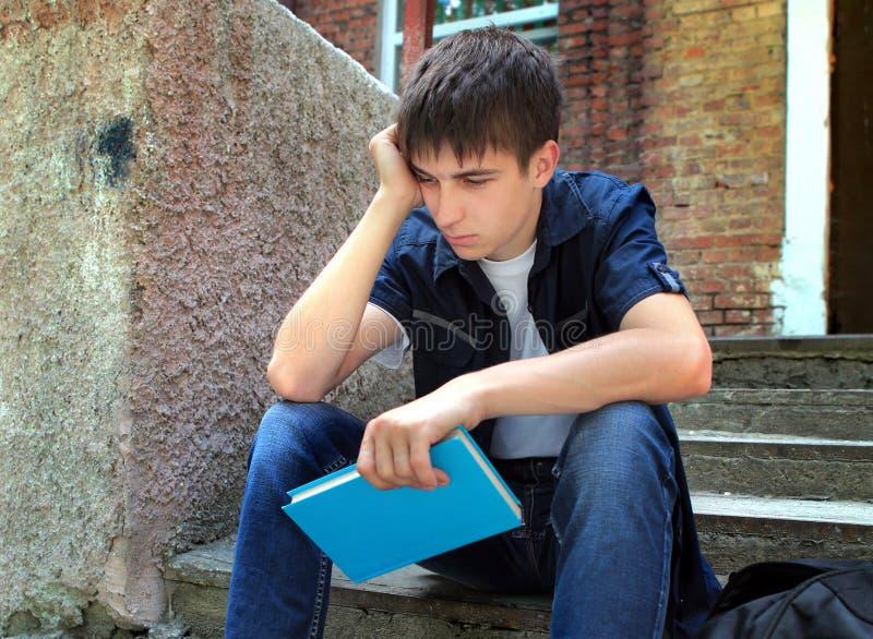 Studente triste con un libro immagini stock libere da diritti