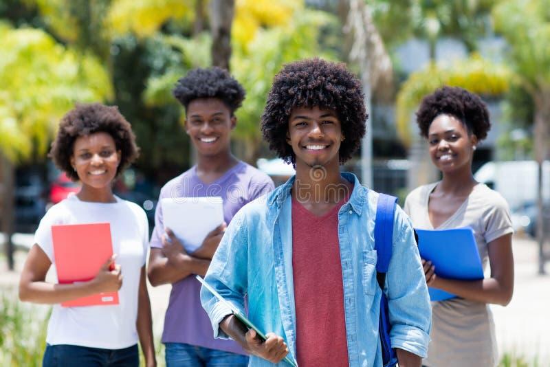 Studente universitario afroamericano con il gruppo di studenti afroamericani fotografia stock libera da diritti