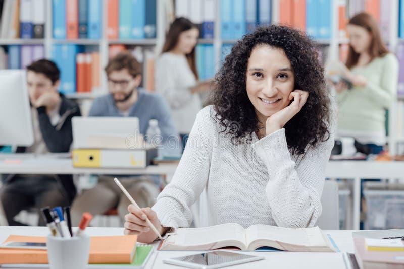 Studente universitario che legge un manuale fotografia stock