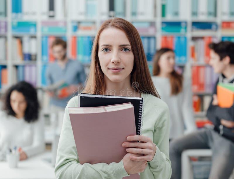 Studente universitario che posa con i taccuini fotografia stock