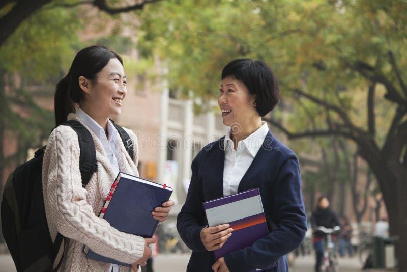 Studente universitario ed il professor sulla città universitaria immagine stock