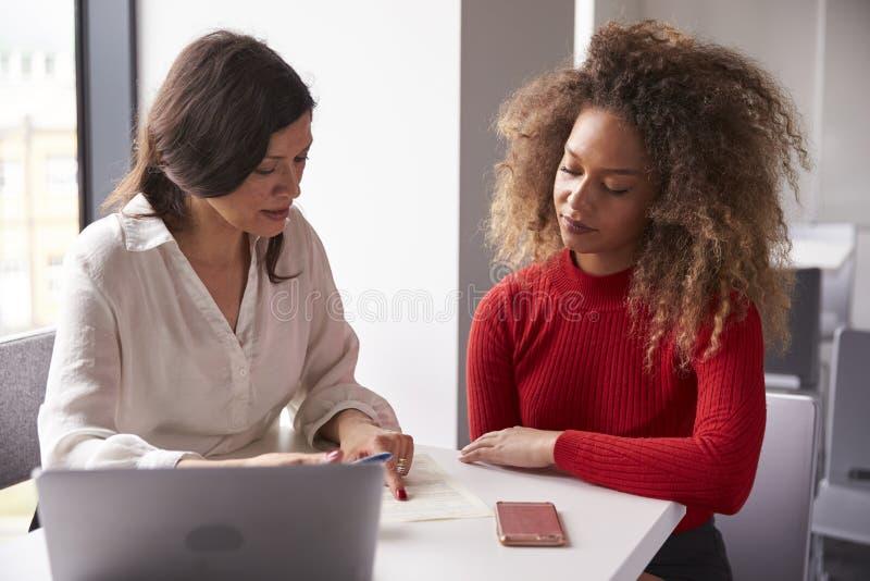 Studente universitario femminile Working One To uno con l'istitutore immagini stock libere da diritti