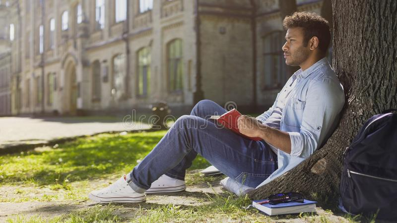 Studente universitario maschio che si siede sotto l'albero, libro di lettura, memorizzante informazioni fotografia stock libera da diritti
