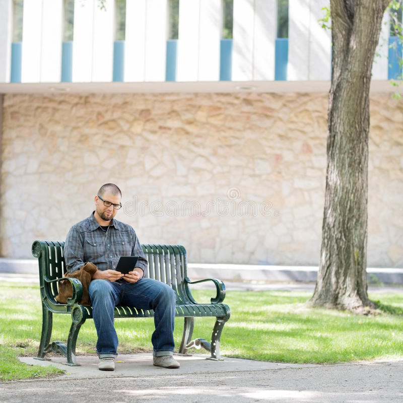 Studente universitario Using Digital Tablet sul banco immagini stock