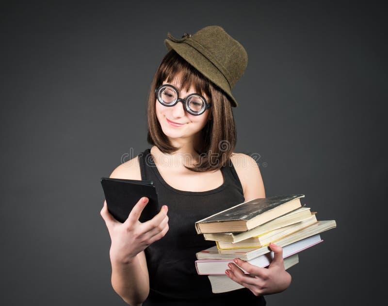 Studente in vetri divertenti con i vecchi libri in un mano ed e-lettore in un altro su fondo grigio La ragazza del nerd sta confr immagini stock libere da diritti