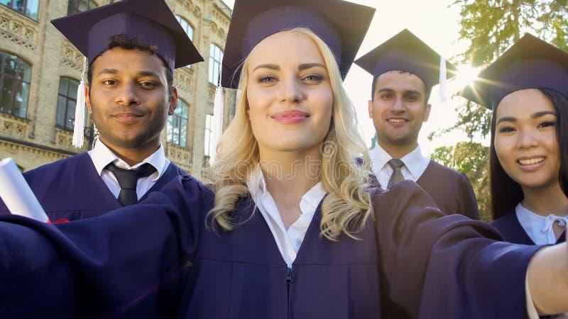 Studenten in academische regalia die selfie op graduatiedag nemen, voltooiing royalty-vrije stock foto's